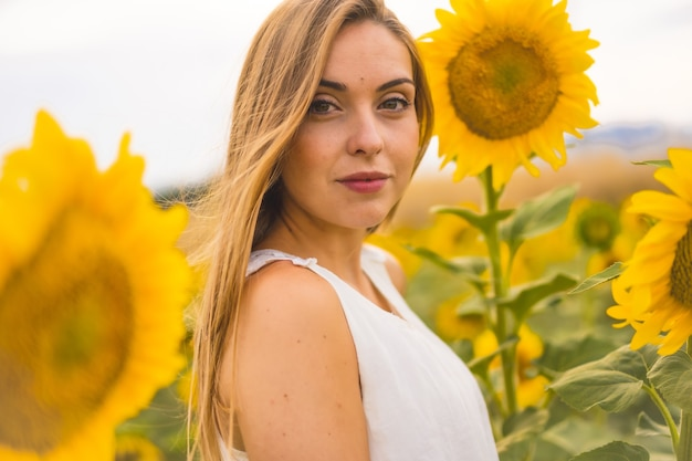 Closeup shot of an attractive blonde model in a white dress posing in a sunflower field