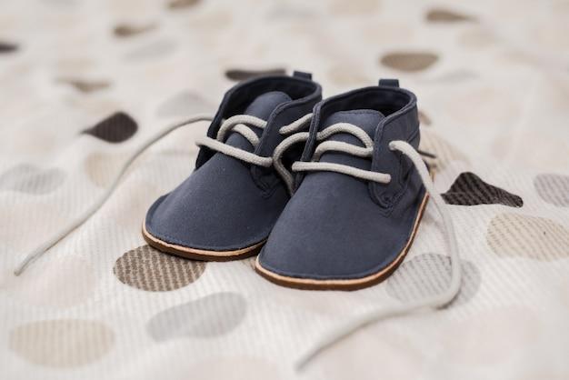 Colpo del primo piano delle scarpe del neonato su un letto