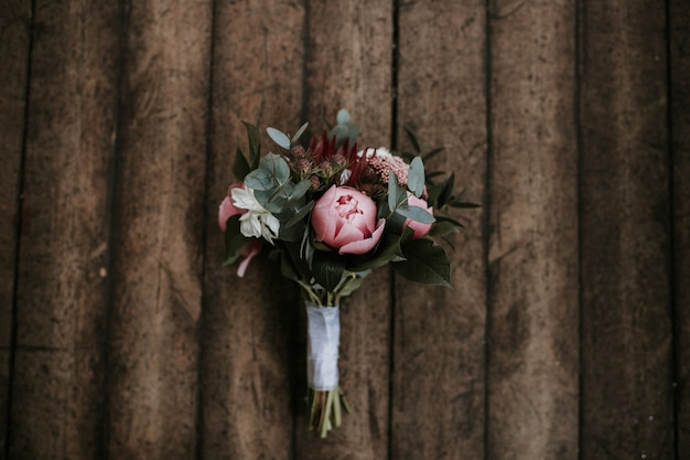 Colpo del primo piano di un bellissimo bouquet di fiori su una superficie in legno
