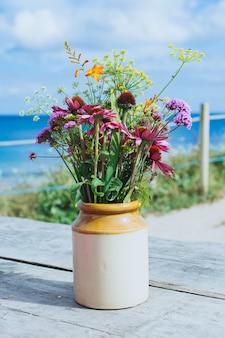 Colpo del primo piano di un bel vaso di fiori con fiori sulla tavola di legno