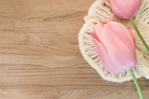 Closeup shot of beautiful pink tulips on wooden background