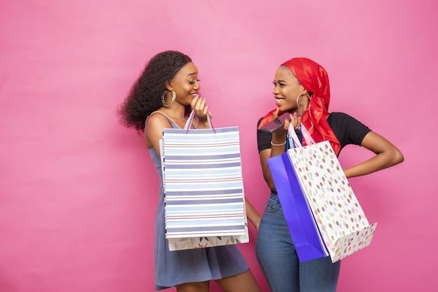 Colpo del primo piano di belle giovani donne africane con le borse della spesa