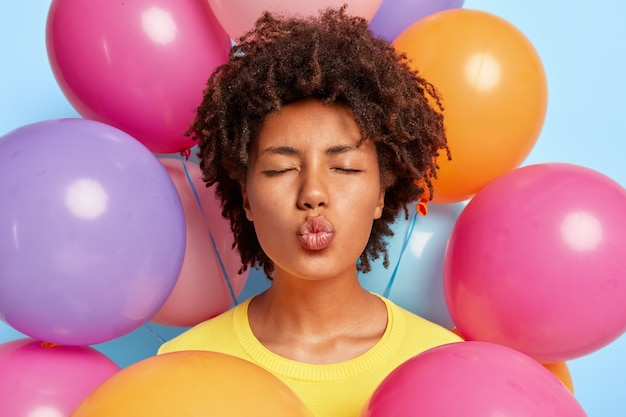Closeup shot of beautiful young woman posing surrounded by birthday colorful balloons