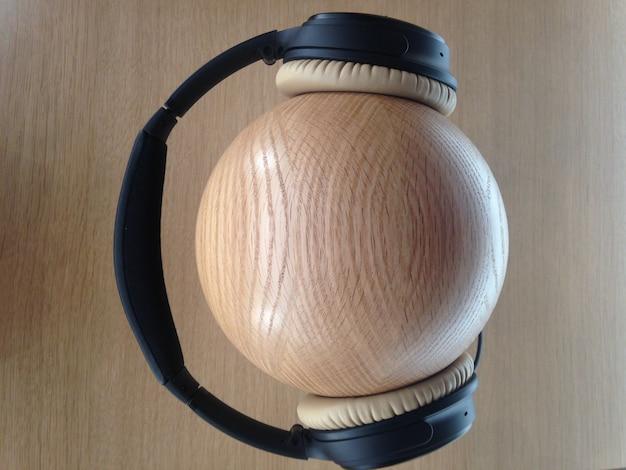 Closeup shot of black headphones on a wooden ball