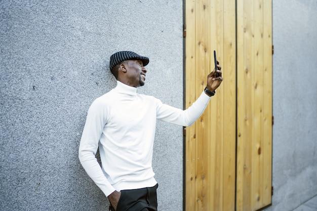 Primo piano di un uomo di colore che indossa un cappello e un dolcevita che si fa un selfie