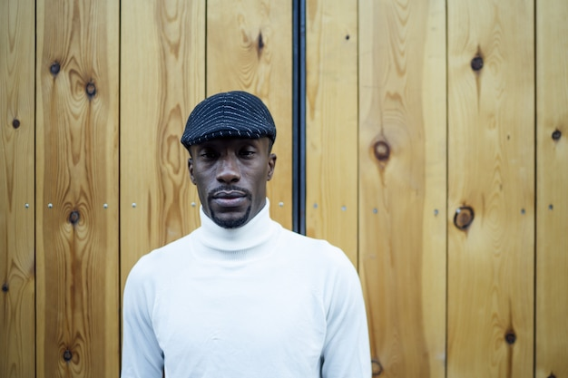 Closeup shot of a black man wearing a hat and a turtleneck