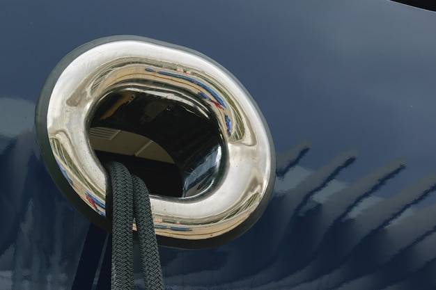Closeup shot of black mooring rope through a round yacht window