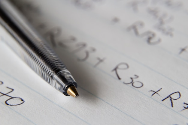 Closeup shot of a black pen on a piece of paper with some numbers and codes written on it