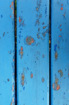 Closeup shot of a blue weathered rusty metal wall with chipped paint