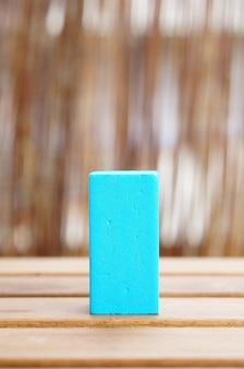 Colpo del primo piano di un blocco di legno blu del giocattolo su una superficie di legno