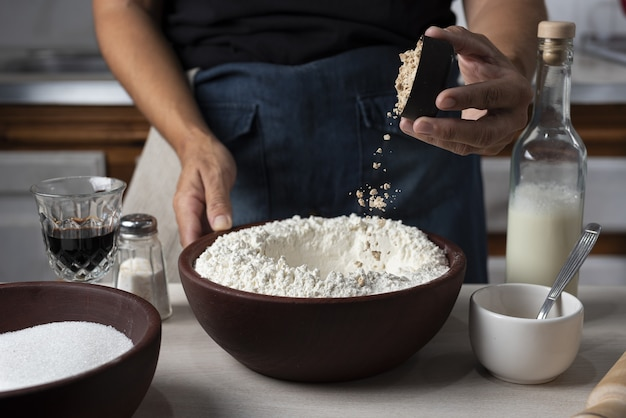 Closeup shot of a bowl full of flour with a person pouring an ingredient in it