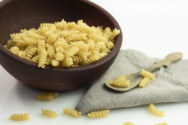 Closeup shot of a bowl of fusilli pasta with a wooden spoon on a gray fabric
