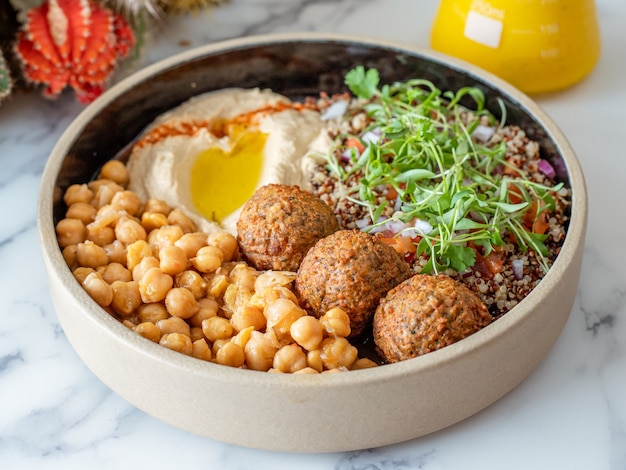 Closeup shot of a bowl of meatballs with chickpeas, grain, and egg