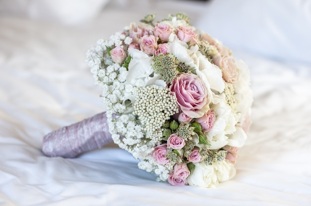 Closeup shot of a bridal bouquet on a white sheet with white, pink and green colors