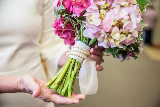 Closeup shot of a bridal flower bouquetmade from various flowers of the shades of pink