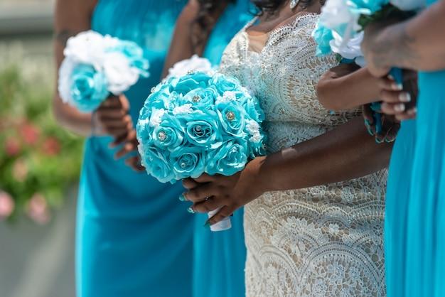 Colpo del primo piano della sposa e delle sue damigelle in piedi e in possesso di mazzi di fiori, nessun volto catturato