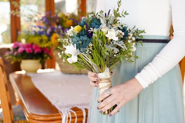 Colpo del primo piano della sposa che tiene il bouquet con bellissimi fiori