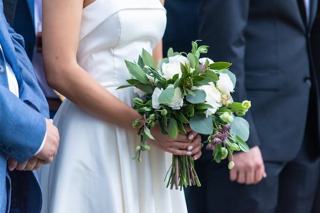 Colpo del primo piano di una sposa che tiene il suo bellissimo bouquet in piedi presso l'altare