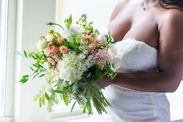 Closeup shot of a bride in a white dress holding a flower bouquet
