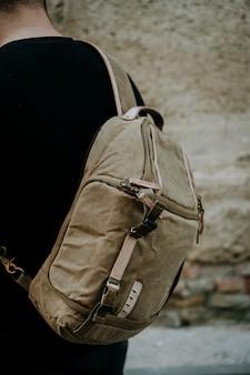Colpo del primo piano di una borsa della macchina fotografica di tela marrone indossata