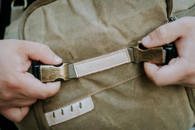 Colpo del primo piano della fibbia e della cinghia di una borsa multiuso della fotocamera in tela marrone