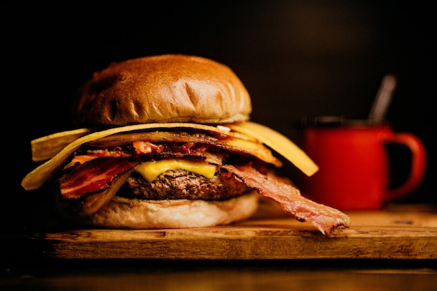 Closeup shot of a burger with bacon and cheese, a red coffee mug