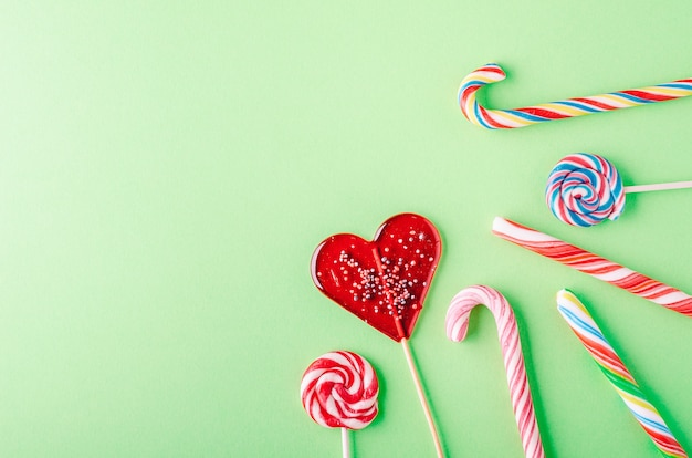 Closeup shot of candy canes and lollipops on a green background