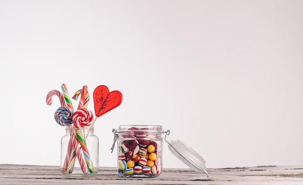 Colpo del primo piano di bastoncini di zucchero e altre caramelle in barattoli di vetro su una superficie di legno