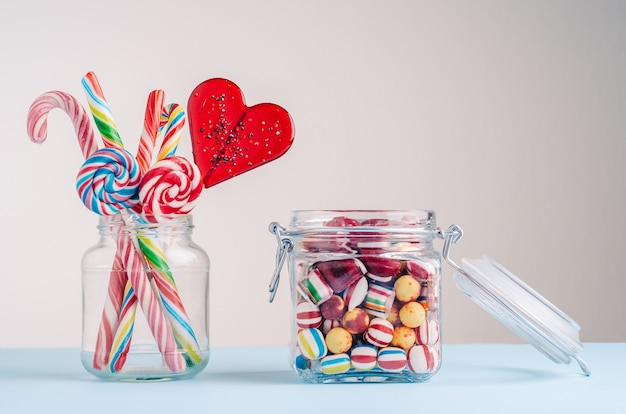 Closeup shot of candy canes and other candies in glass jars