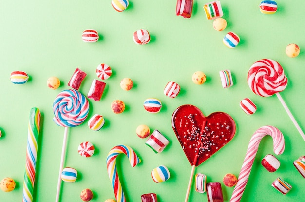 Closeup shot of candy canes and other candies on a green background