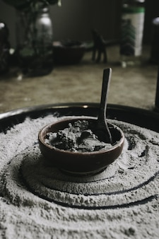 Closeup shot of a ceramic cooking pot with ingredients and a spoon in it with flour around