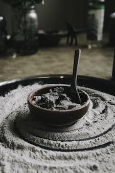 Colpo del primo piano di una pentola di cottura in ceramica con ingredienti e un cucchiaio in esso con farina intorno