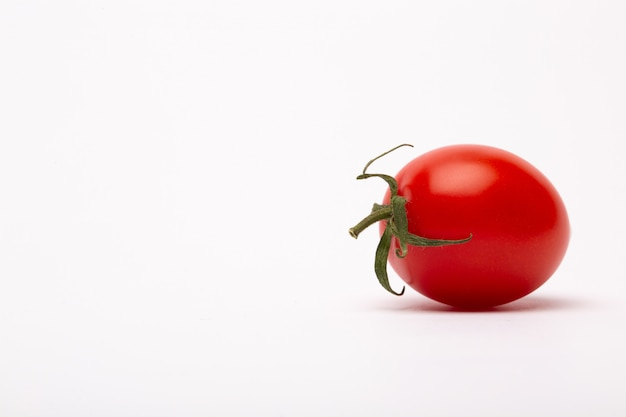 Closeup shot of a cherry tomato on a white wall - perfect for a food blog