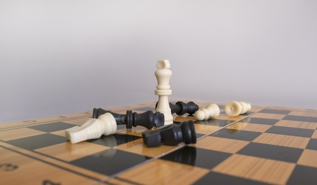Closeup shot of chess figurines on a chessboard with a blurred white background