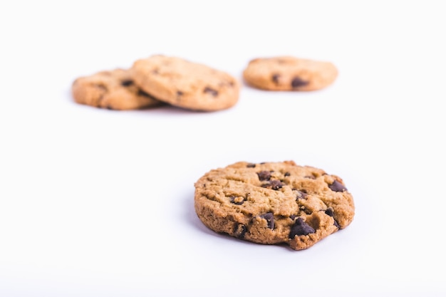 Closeup shot of a chocolate chip cookie with cookies in a blurred white background