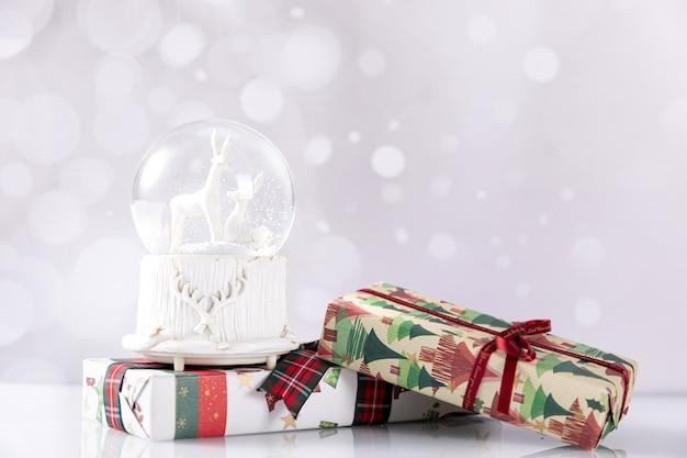 Closeup colpo di scatole regalo di natale e palla di vetro su bokeh