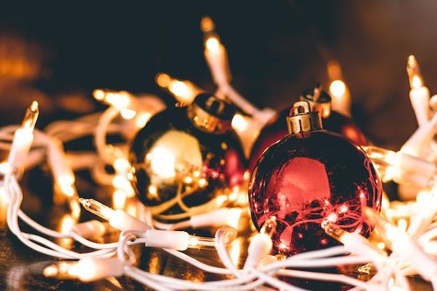 Un primo piano degli ornamenti natalizi circondati dalle luci degli alberi