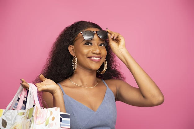 Closeup shot of a classy young afro-american female holding shopping bags on a pink