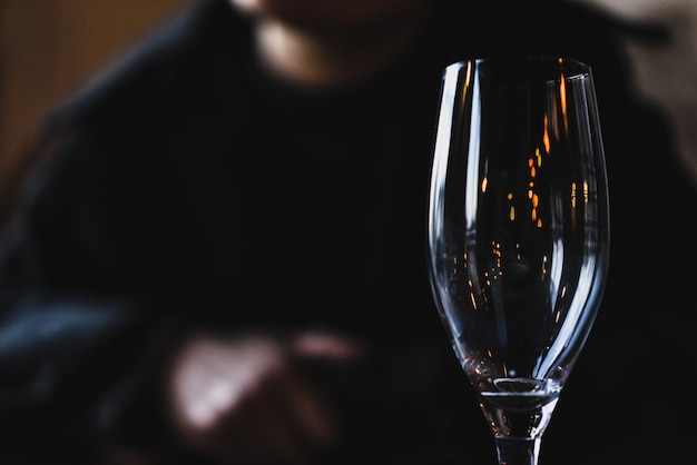 Closeup shot of a clear champagne glass with a person blurred in the