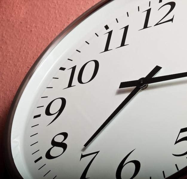 Closeup shot of a clock on a coral wall