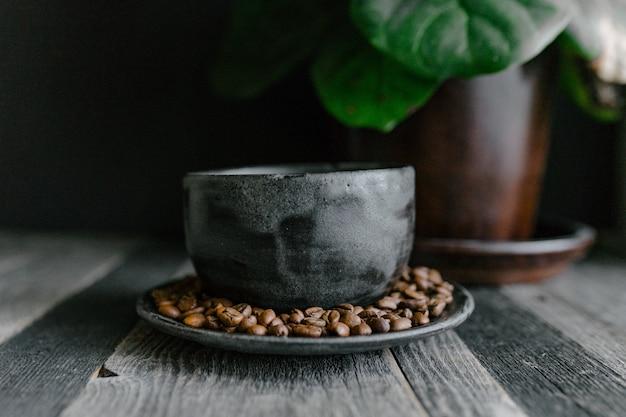 Il primo piano ha sparato dei chicchi di caffè su un piatto dell'argilla su una tavola di legno