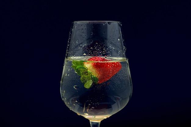 Colpo del primo piano di un cocktail freddo di vetro della vite con una fragola su un buio