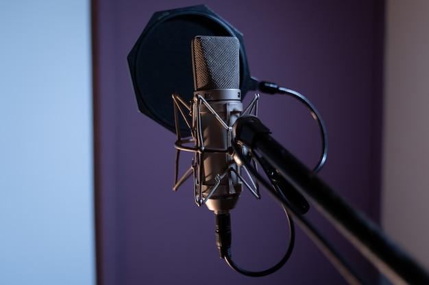 Closeup shot of a condenser microphone with a pop filter and a blurred