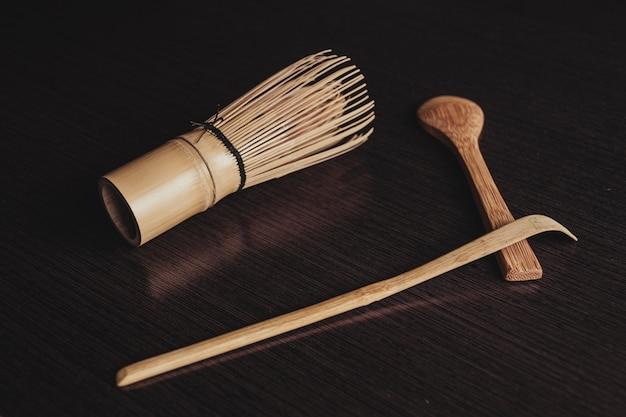Colpo del primo piano di una spazzola da cucina con cucchiai di legno su sfondo nero