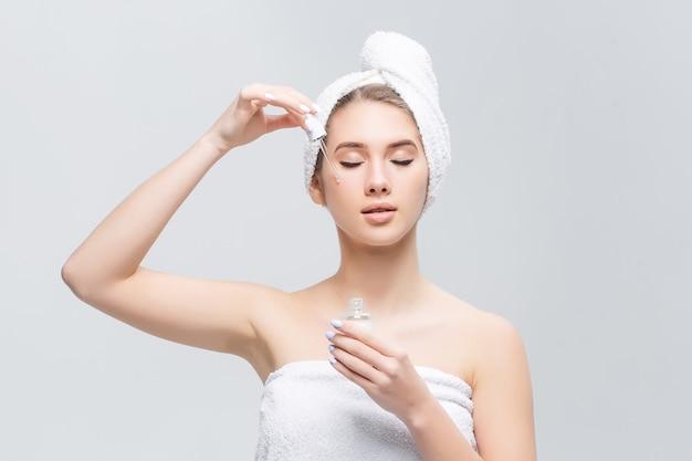 Colpo del primo piano dell'olio cosmetico che si applica sul fronte della giovane donna con la pipetta