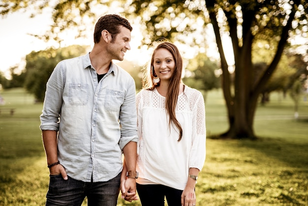 Closeup shot of a couple holding hands while smiling with a blurred background