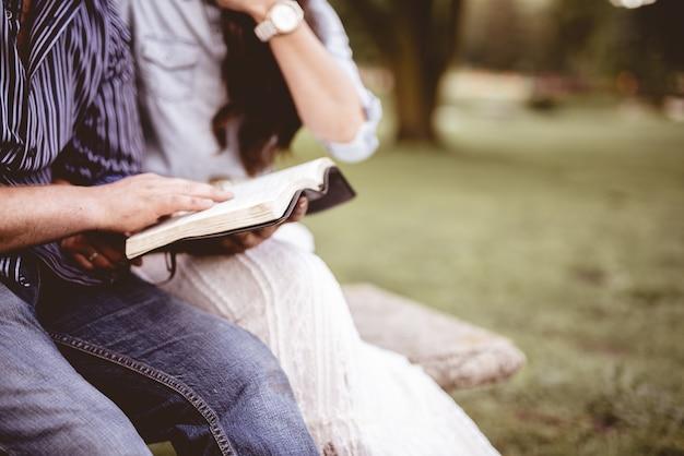 Colpo del primo piano di una coppia seduta nel parco e leggendo la bibbia con uno sfondo sfocato