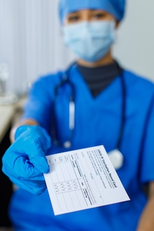 Closeup shot of covid-19 vaccination record card certificate passport paper sent to patient by doctor wears blue hospital uniform face mask rubber gloves and stethoscope in blurred background.
