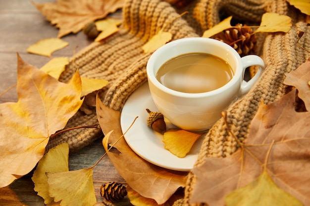 Closeup shot of a cup of coffee and autumn leaves on wooden background