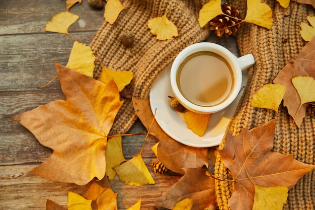 Primo piano di una tazza di caffè e foglie autunnali su una superficie di legno